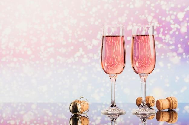 Dos copas de champán rosa y decoración de navidad o año nuevo y corchos con nieve ligera bokeh de fondo. cena romántica. concepto de vacaciones de invierno.