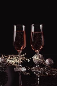 Dos copas de champán rosa y decoración de navidad o año nuevo sobre un fondo negro. cena romántica. concepto de vacaciones de invierno.