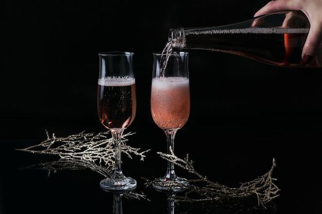 Dos copas de champán rosa y decoración de navidad o año nuevo sobre fondo negro. mano de mujer sostiene una botella y champán vertido. cena romántica. concepto de vacaciones de invierno.