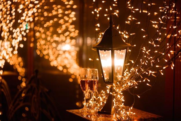 Dos copas de champán sobre desenfoque de fondo de luces de puntos. celebración, espacio libre para texto.