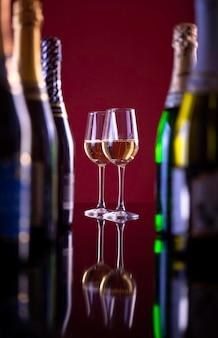 Dos copas de champán sobre un fondo burdeos. un vaso junto a botellas de alcohol