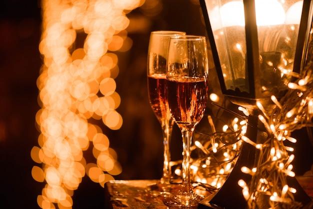 Dos copas de champán sobre manchas borrosas luces borrosas celebración