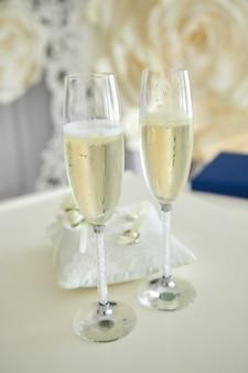 Dos copas de champaña y almohada con anillos de boda