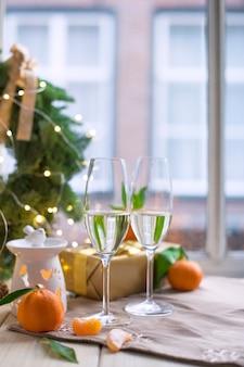 Dos copas de champaña, fruta en la mesa junto a la ventana