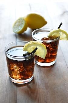Dos copas de cóctel cuba libre con limón y menta.