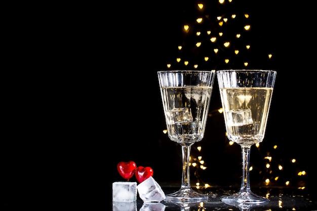 Dos copas con un cóctel y dos corazones, concepto de día de san valentín.