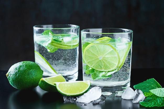 Dos copas de cóctel con limón y menta sobre fondo oscuro