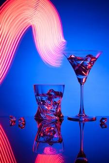 Dos copas de cóctel martini whisky hielo, contra el azul de hermosos efectos de luz.
