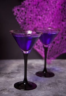 Dos copas con cóctel morado para la fiesta de halloween en la oscuridad