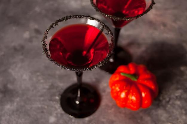 Dos copas con cóctel rojo para la fiesta de halloween en la oscuridad