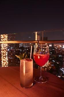 Dos copas de cóctel en la terraza de la azotea con vista aérea nocturna de la ciudad