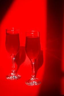 Dos copas de cóctel con vino tinto espumoso sobre fondo rojo en la luz del sol natural con sombras. composición de arte creativo minimalista. imagen conceptual. concepto visual simple.