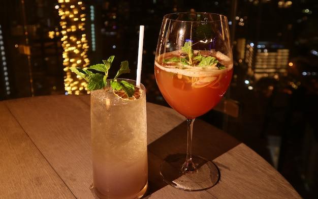 Dos copas de diferentes tipos de cócteles en el bar de la azotea con luces bokeh