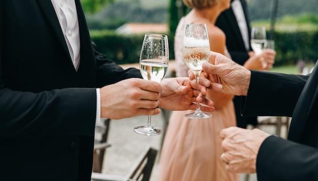 Dos copas de hombre con champán de pie en el pasillo durante