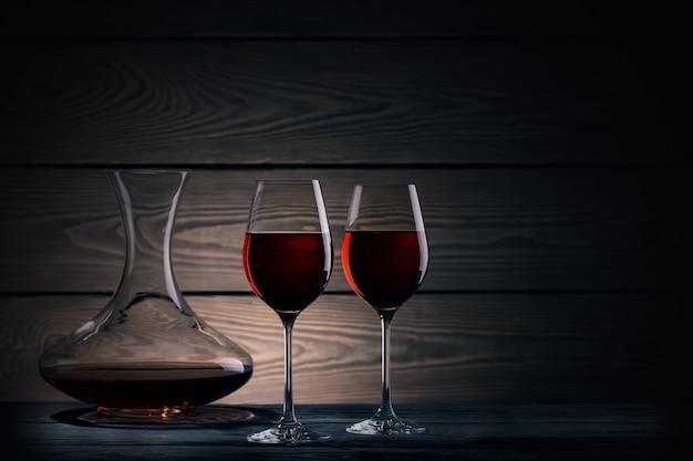 Dos copas y jarra de vino tinto en la oscuridad
