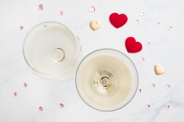 Dos copas de vino blanco y corazones