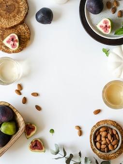Dos copas de vino blanco, higos y almendras sobre un fondo blanco.