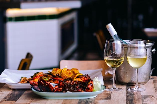 Dos copas de vino blanco sobre la mesa con una botella en un cubo de enfriador de vino y un plato de mariscos para una cena de pareja.