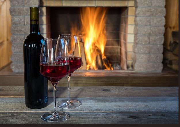 Dos copas de vino y botella de vino junto a la acogedora chimenea, en casa de campo.