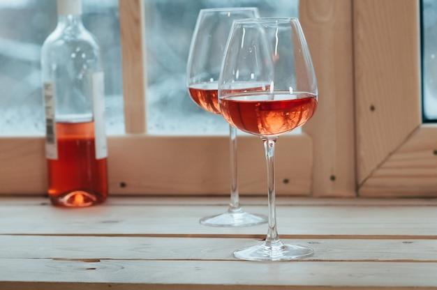 Dos copas de vino y una botella de vino rosado en el alféizar de una ventana