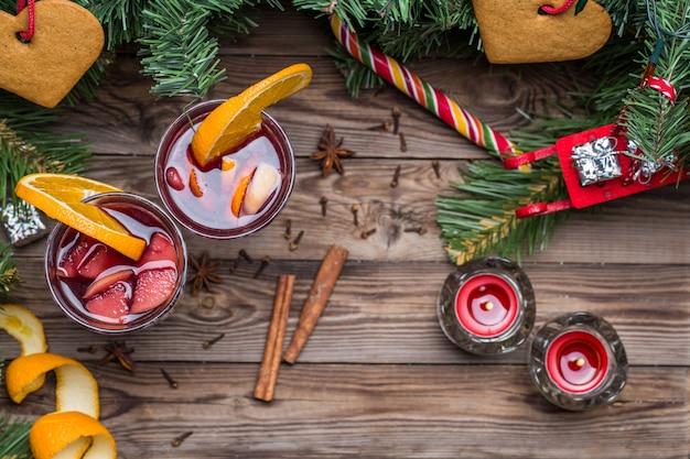 Dos copas de vino caliente caliente con naranjas, manzanas y especias