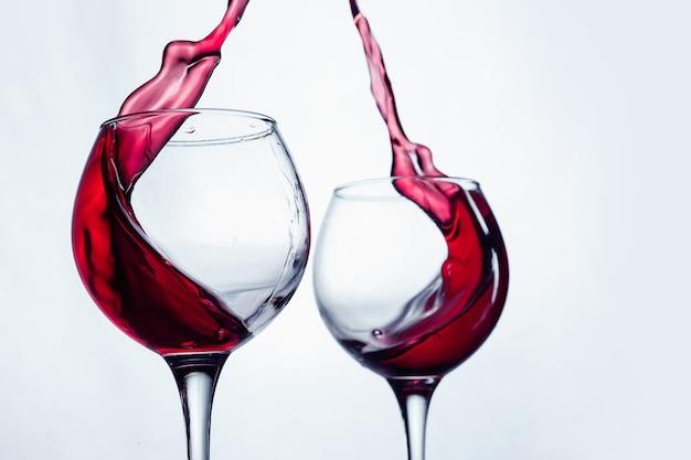 Dos copas de vino en gesto de tostado con grandes salpicaduras en el estudio.