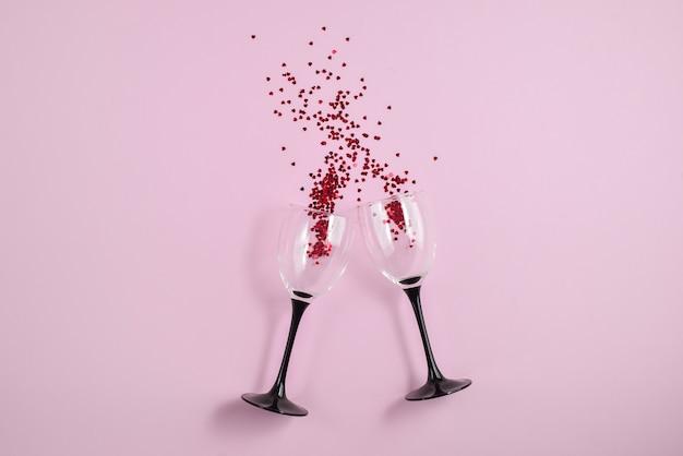 Dos copas de vino que tintinean derramaron confeti rojo del corazón en fondo rosado del papel del color.