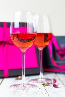 Dos copas de vino rosado en la mesa de madera blanca con cajas de regalo rosa