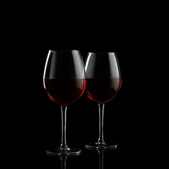 Dos copas de vino tinto en la oscuridad.