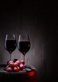 Dos copas de vino tinto y racimo de uvas en barrica
