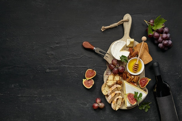 Dos copas de vino tinto y un sabroso plato de queso con fruta, uva, nueces y pan tostado en el escritorio negro.