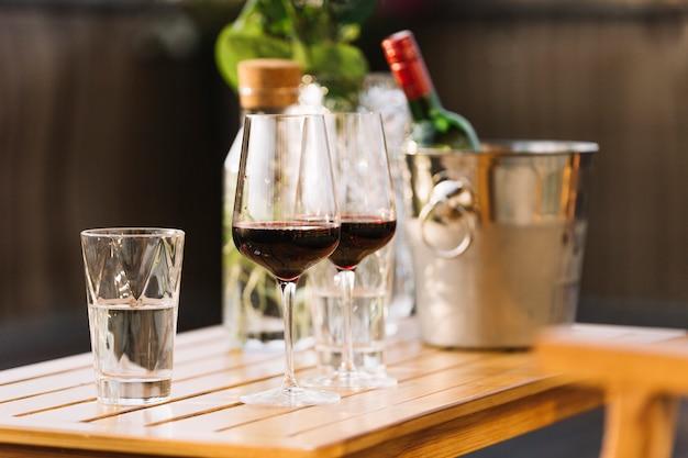 Dos copas de vino tinto y vaso de agua en la mesa de madera