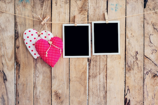 Dos corazón y marco de la foto dos que cuelgan en cuerda de la cuerda para tender la ropa con el fondo de madera.