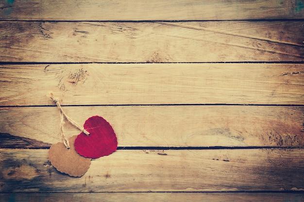 Dos corazón rojo y marrón sobre fondo de madera con estilo vintage.