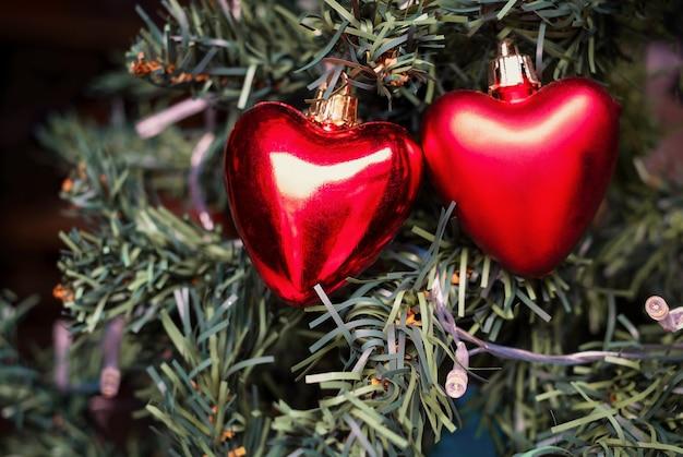 Dos corazones adornados de navidad en el árbol de navidad
