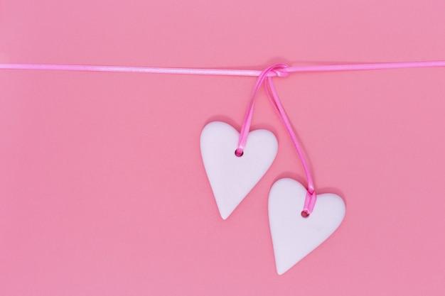 Dos corazones blancos juntos sobre fondo rosa. concepto de vacaciones para la boda o el día de san valentín.
