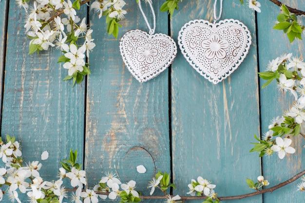 Dos corazones calados y ramas de cerezo en flor.