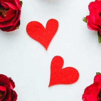 Dos corazones de fieltro rojo sobre fondo blanco con flores de papel rojo.