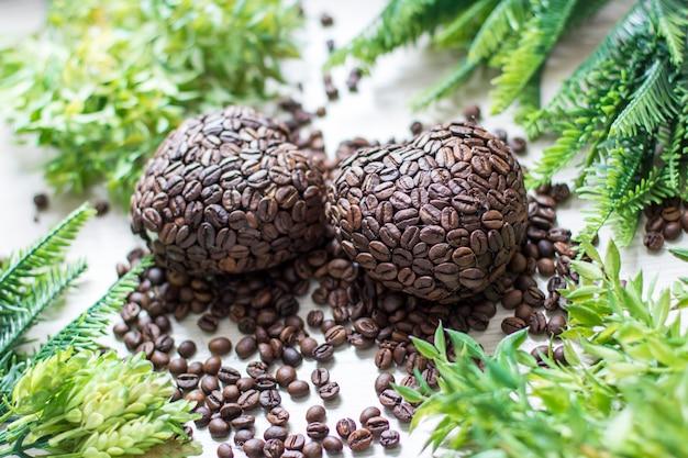 Dos corazones de granos de café y ramas verdes.