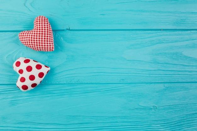 Dos corazones hechos a mano en superficie turquesa.
