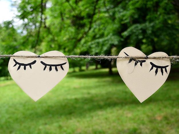 Dos corazones de papel que cuelgan en una cuerda, concepto del día de tarjeta del día de san valentín.