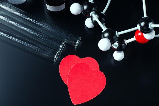 Dos corazones de papel rojos y un modelo de estructura molecular sobre un negro. concepto de química del amor