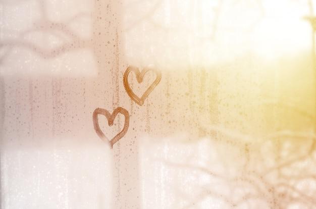 Dos corazones pintados en un vidrio empañado en invierno