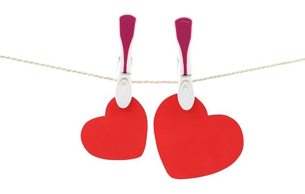 Dos corazones rojos colgando de una cuerda con pinzas para la ropa, aislados en blanco.