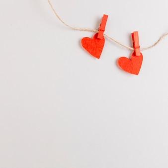 Dos corazones rojos en una cuerda con alfileres
