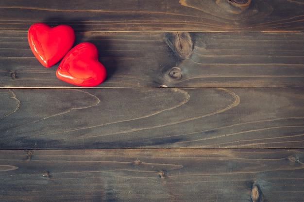 Dos corazones rojos sobre fondo de mesa de madera con espacio de copia