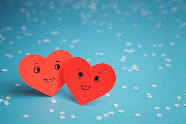 Dos corazones rojos sonrientes en una mesa azul. día de san valentín. pareja enamorada.