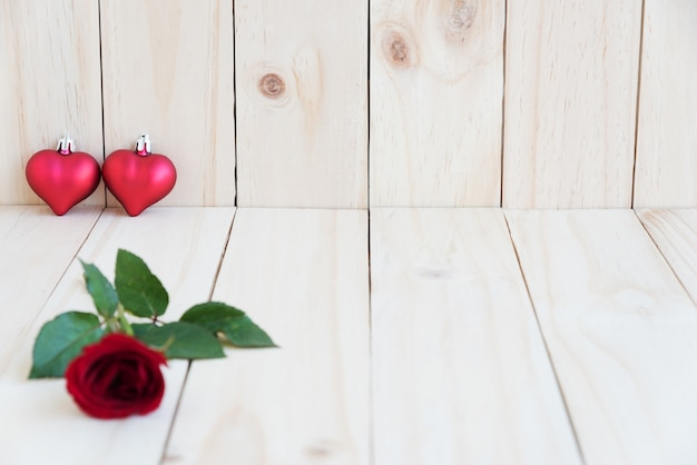 Dos corazones y rosa roja sobre fondo de madera