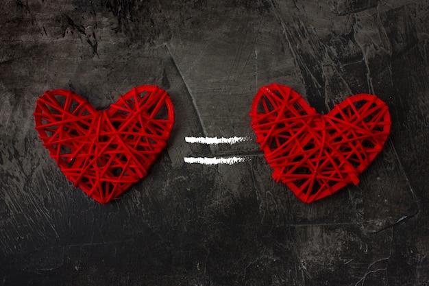 Dos corazones con el signo igual en la oscuridad.