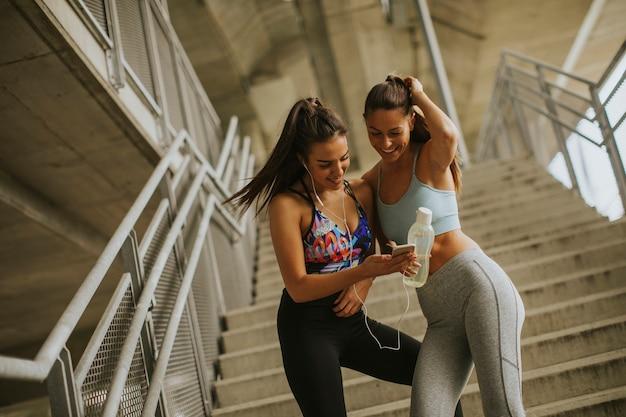 Dos corredores femeninos que buscan en el teléfono inteligente un descanso después de trotar